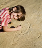 Little girl and the heart in sand Royalty Free Stock Photo