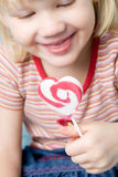 Little girl with a heart shape lollipop. Cute little girl with a heart shape lollipop Stock Photo