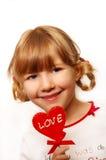 Little girl with heart shape lolly Stock Photos