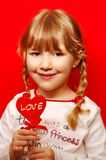 Little girl with heart shape lolly Stock Image