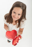 Little girl with heart shaped gift box. Little girl holding a heart shaped gift box Stock Image