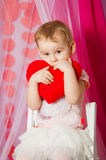 Little girl with a heart toy in pink  skirt. Little girl with a heart toy in pink tutu skirt Royalty Free Stock Photo