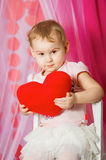 Little girl with a heart toy in pink  skirt. Little girl with a heart toy in pink tutu skirt Royalty Free Stock Image