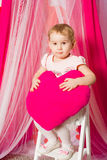Little girl with a heart toy in pink  skirt. Little girl with a heart toy in pink tutu skirt Stock Photography
