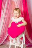 Little girl with a heart toy in pink  skirt. Little girl with a heart toy in pink tutu skirt Royalty Free Stock Photography
