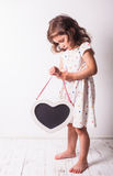 The little girl with a heart. Little girl in a white polka-dot dress holding a wooden heart shaped chalkboard Stock Image
