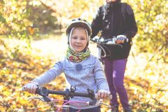 Little girl in the helmet with the bicycle in the autumn forest stock photography