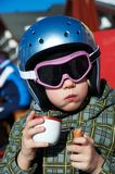 Little girl in helmet and glasses eats and drink Stock Image