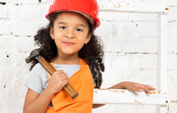 Little girl in helmet with hammer and screwdriver Stock Photo