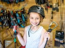 Little girl in helmet holding climbing equipment in hands Royalty Free Stock Photo