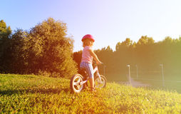 Little girl with helmet riding bike at sunset Stock Photography