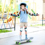 Little girl with a helmet riding on skateboard Royalty Free Stock Photography