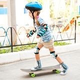 Little girl with a helmet riding on skateboard