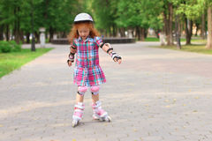 Little girl in helmet roller skates in green summer park Stock Image