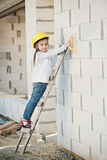 Little girl with helmet working on construction Stock Photo