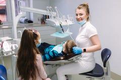 Little girl help female dentist, new teeth examinationand treatment of cavities.  royalty free stock photos