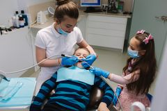 Little girl help female dentist, new teeth examinationand treatment of cavities.  royalty free stock images