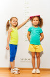 Little girl help friend to measure height on scale. Two girls standing by the scale on the wall and fixating the height with book looking at camera and smiling royalty free stock image