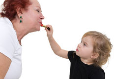 Little girl help grandma with her makeup Stock Photo