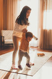 Little girl helping baby sister to walk Stock Images