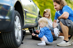 Little girl helping father to change a car wheel Stock Photo