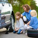 Little girl helping father to change a car wheel Royalty Free Stock Images