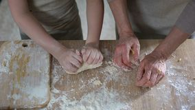 Little girl helping grandmother to roll dough for pizza, family recipe, cooking. Stock photo stock image