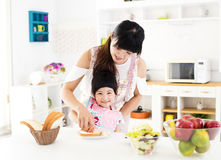 Little girl helping her mother prepare food in the kitchen Royalty Free Stock Photo