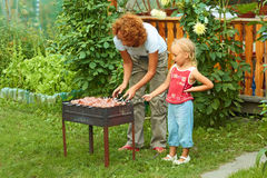 Little girl helping her mother to cook shish kebab Royalty Free Stock Photo