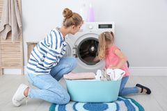 Little girl helping her mother to do laundry. At home stock photo