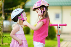 Little girl helping her sister to put a helmet on Stock Photography