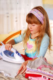 Little girl helping with ironing. Little girl helping her mother with ironing baby clothes Royalty Free Stock Photos