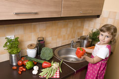 Little girl helping in kitchen stock photos