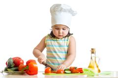 Little girl helping at kitchen with salad making Stock Images