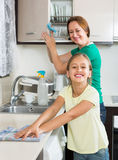 Little girl helping mother at kitchen Stock Images