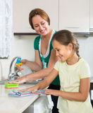 Little girl helping mother at kitchen Stock Image