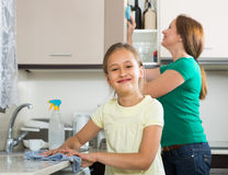 Little girl helping mother at kitchen Royalty Free Stock Photography