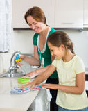 Little girl helping mother at kitchen Stock Photos