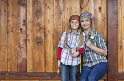 Little girl helping mother repainting the wood shed Stock Image