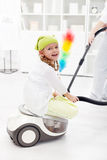 Little girl helping mother to clean the room. Sitting on the vacuum cleaner Stock Photography