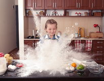 Little girl is helping to bake  in a messy  kitchen Royalty Free Stock Photography