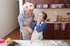 Little girl is helping to bake  in a messy  kitchen Royalty Free Stock Image