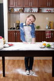 Little girl is helping to bake  in a messy  kitchen Royalty Free Stock Images