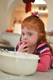 Little Girl Helps Bake. Small female child helping bake cookies and sneaking a taste of the icing Royalty Free Stock Image