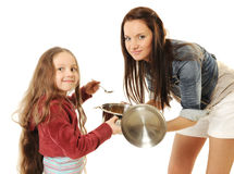 Little girl helps his mother to cook Stock Photos