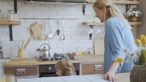 Little girl helps mom bake cookies in the kitchen. girl takes out cookies with chocolate from the oven using kitchen. Potholders stock footage