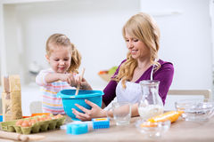 Little girl helps mother in the kitchen Stock Photos