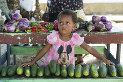 Little girl helps to sell fresh vegetables Stock Photos