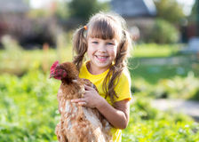 Little girl with a hen in the front yard stock photo