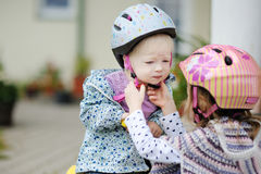Little girl hepling her sister to put a helmet Royalty Free Stock Photos